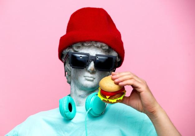 Antykwarskie popiersie samiec w kapeluszu i okularach przeciwsłonecznych z hamburgerem