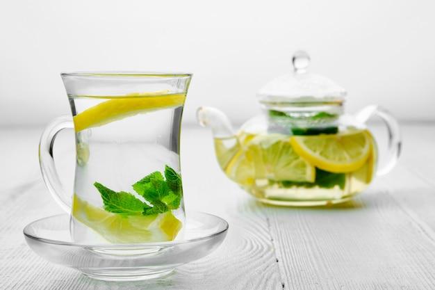 Antyoksydacyjny gorący napój z cytryną i miętą w przezroczystym dzbanku do herbaty i szkle