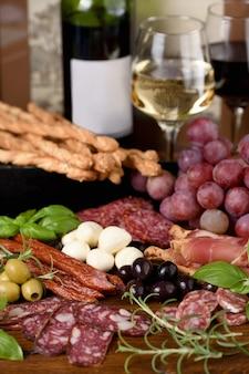 Antypasto. danie z kiełbasą, suszoną szynką, salami, chrupiącym grissini z winogronami. mięsna przystawka to świetny pomysł na wino.