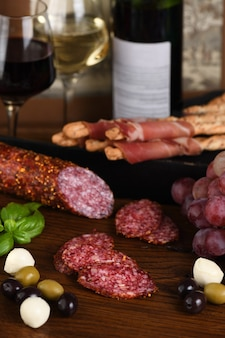 Antypasto. szynka suszona, salami, chrupiące grissini z winogronami. mięsna przystawka to świetny pomysł na wino.