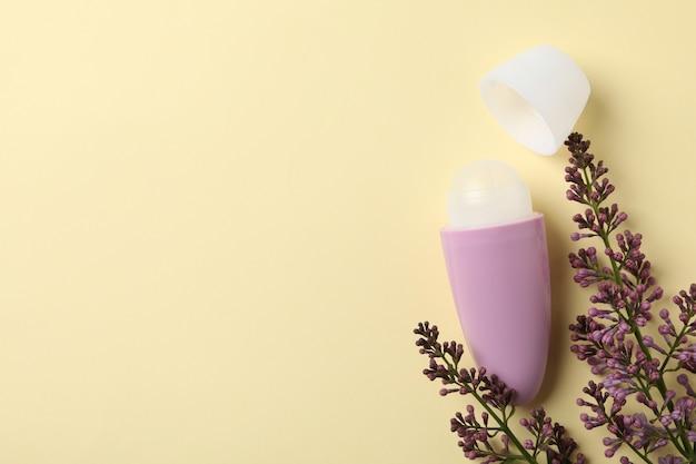 Antyperspirant do ciała w kulce i liliowy dezodorant na beżowym tle, miejsce na tekst