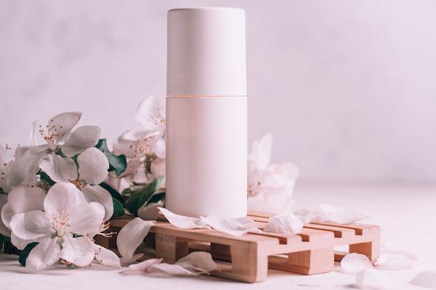 Antyperspirant w kulce na drewnianym podium w formie palety na jasnej gipsowej powierzchni z kwiatami jabłoni. skopiuj miejsce