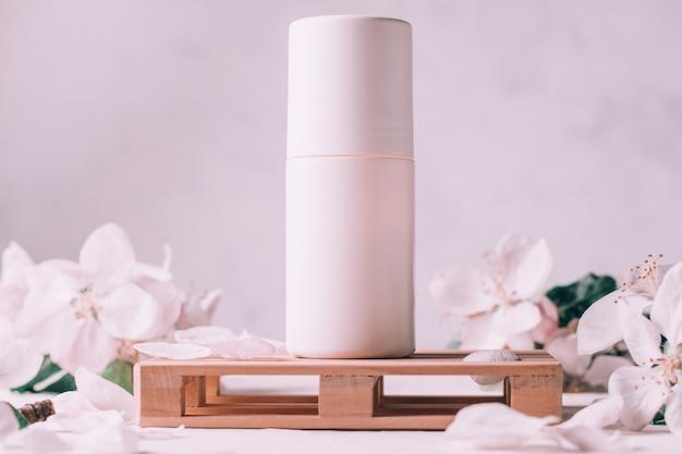 Antyperspirant w kulce na drewnianym podium w formie palety, na jasnej powierzchni gipsowej z kwiatami jabłoni