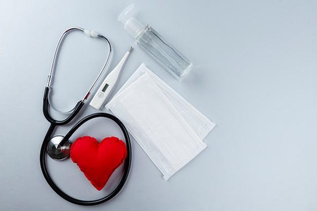 Antyseptyczny żel do higieny osobistej, maski, termometr i stetoskop. szara ściana. koncepcja higieny osobistej.