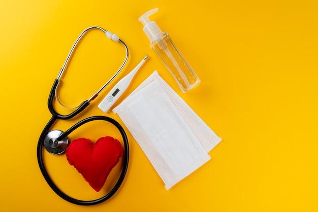 Antyseptyczny żel do higieny osobistej, maski, termometr i stetoskop. żółta ściana. koncepcja higieny osobistej.