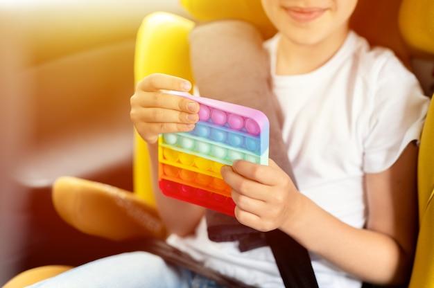 Antystresowe sensoryczne zabawki pop it w dziecięcych rękach mała dziewczynka bawi się zabawką w samochodzie