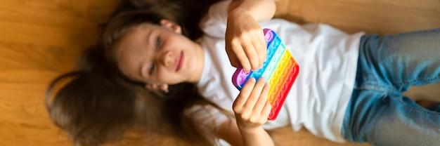 Antystresowe zabawki sensoryczne pop it w dziecięcych rękach. mała szczęśliwa dziewczynka bawi się w domu prostą zabawką z dołeczkiem. maluch trzymający i bawiący się kolor tęczy popit, trend 2021 rok. transparent