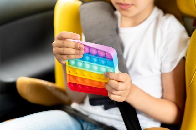 Antystresowe zabawki sensoryczne pop it w dziecięcych rękach. mała szczęśliwa dziewczynka bawi się w samochodzie prostą zabawką z dołeczkiem.