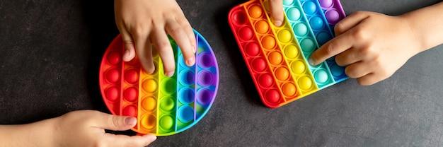Antystresowe zabawki sensoryczne pop it w dziecięcych rękach. małe szczęśliwe dzieci bawią się prostą zabawką z dołeczkami na czarnym stole. małe dzieci trzymające i bawiące się kolorem tęczy popit, trend 2021 rok. transparent