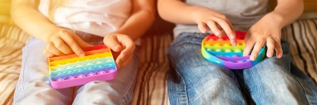 Antystresowe zabawki sensoryczne pop it w dziecięcych rękach. małe szczęśliwe dzieci bawią się w domu prostą zabawką z wgłębieniami. małe dzieci trzymające i bawiące się kolorem tęczy popit, trend 2021 rok. transparent. migotać