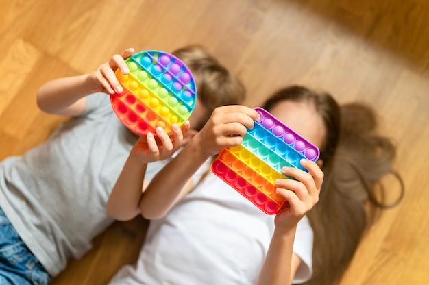 Antystresowe zabawki sensoryczne pop it w dziecięcych rękach. małe szczęśliwe dzieci bawią się w domu prostą zabawką z wgłębieniami. małe dzieci trzymające i bawiące się popit tęczowy odcień jasny kolor, trend 2021 rok