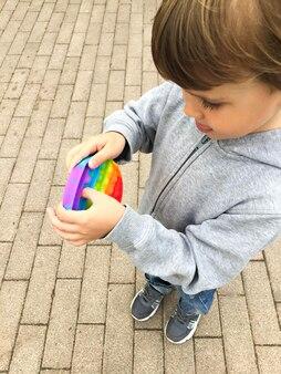 Antystresowe zabawki sensoryczne pop it w dziecięcych rękach. mały szczęśliwy chłopiec bawi się prostą zabawką z dołeczkami na ulicy miasta.