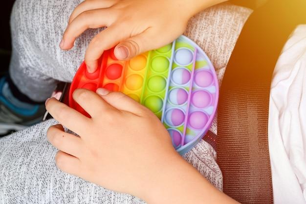 Antystresowe zabawki sensoryczne pop it w dziecięcych rękach. mały szczęśliwy chłopiec bawi się w samochodzie prostą zabawką z dołeczkami. maluch trzyma i bawi się popit tęczowy odcień jasny kolor, trend 2021 rok