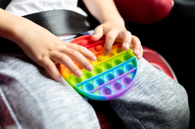 Antystresowe zabawki sensoryczne pop it w dziecięcych rękach. mały szczęśliwy chłopiec bawi się w samochodzie prostą zabawką z dołeczkami.