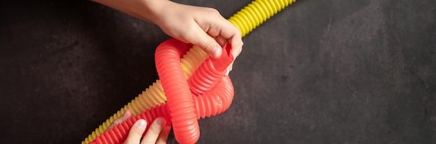 Antystresowe zabawki sensoryczne pop w rękach dzieci. małe szczęśliwe dzieci bawią się zabawką poptube na czarnym stole. małe dzieci trzymające i bawiące się rurkami pop czerwony i żółty jasny kolor. transparent