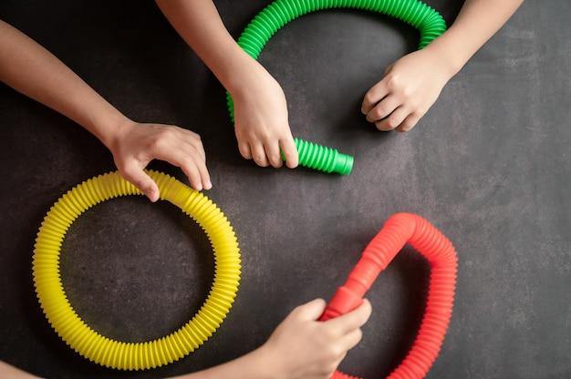 Antystresowe zabawki sensoryczne w kształcie tuby w dziecięcych rękach. małe szczęśliwe dzieci bawią się zabawką poptube na czarnym stole. małe dzieci trzymające i bawiące się rurkami pop wielokolorowy jasny kolor, trend 2021 rok