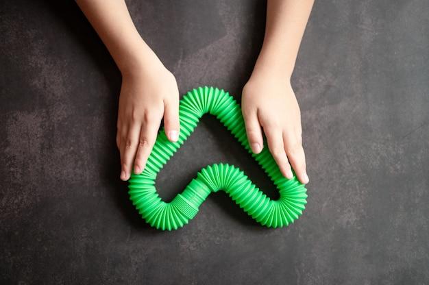 Antystresowe zabawki sensoryczne w kształcie tuby w dziecięcych rękach. małe szczęśliwe dzieci bawią się zabawką poptube na czarnym stole. małe dzieci trzymające i bawiące się rurkami pop zielony jasny kolor, trend 2021 rok