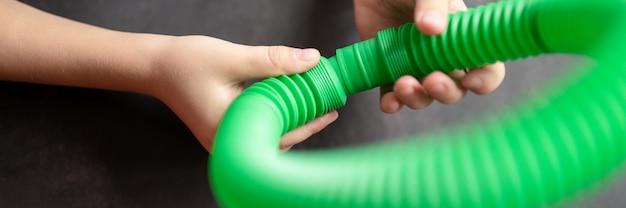 Antystresowe zabawki sensoryczne w kształcie tuby w dziecięcych rękach. małe szczęśliwe dzieci bawią się zabawką poptube na czarnym stole. maluchy trzymające i bawiące się rurkami pop wielokolorowy jasny kolor. transparent
