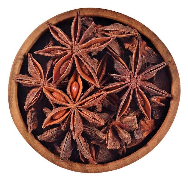 Anyż gwiazdkowaty w drewnianej misce na białym tle