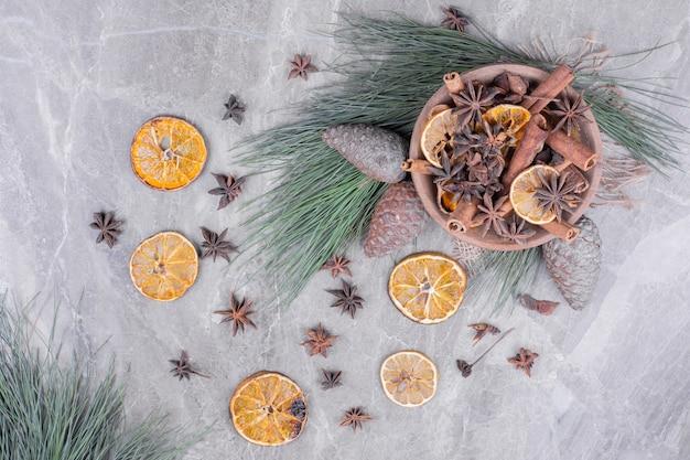 Anyż i cynamony z plastrami pomarańczy w drewnianym kubku