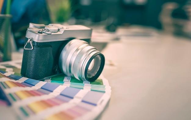 Aparat cyfrowy i próbki kolorów na biurku