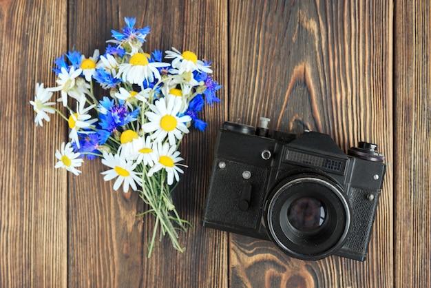 Aparat fotograficzny, notebook, telefon komórkowy i polne kwiaty na ciemnym tle drewnianych. wolny zawód. zarobki na zdjęciu.