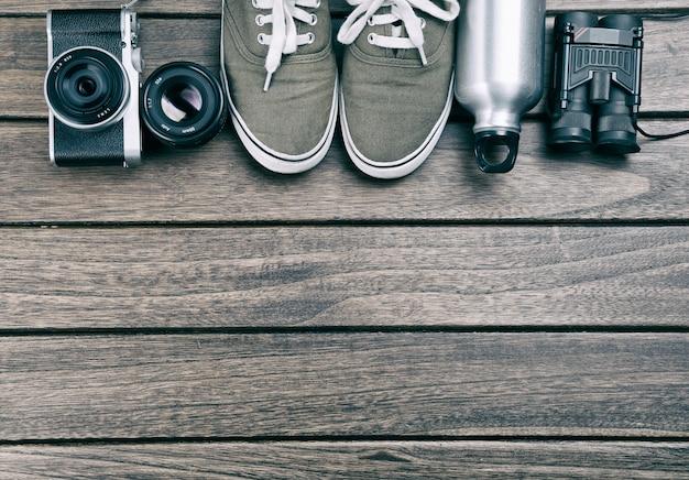 Aparat fotograficzny, obiektyw, lornetki, płótno, butelka sportowa na drewnianym stole retro