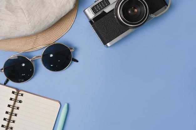 Aparat fotograficzny, okulary przeciwsłoneczne, notatnik i kapelusz na niebieskim tle.