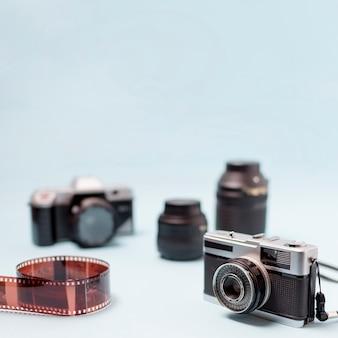 Aparat fotograficzny; soczewka optyczna i zwinięty pasek filmu na niebieskim tle
