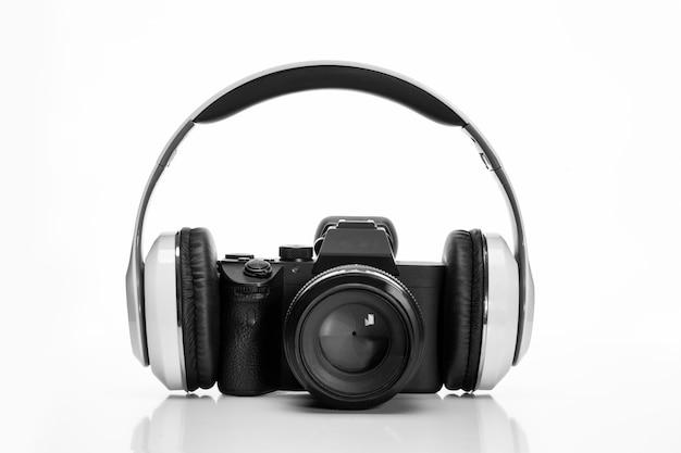 Aparat fotograficzny ze słuchawkami na białym tle