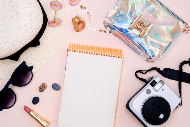 Aparat, kapelusz, okulary i płaski notatnik na jasnej powierzchni