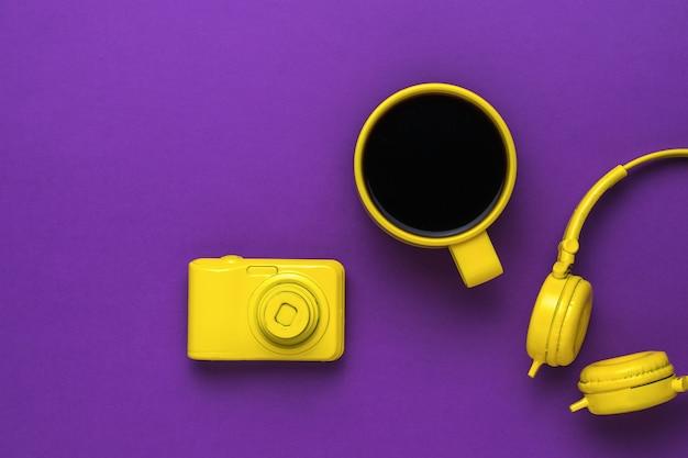 Aparat, kubek kawy i słuchawki na fioletowym tle. trend kolorystyczny.