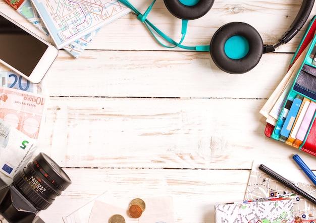 Aparat, mapy turystyczne, słuchawki, portfel z kartami kredytowymi, telefon, kolorowe długopisy, banknoty euro i monety na białym biurku.