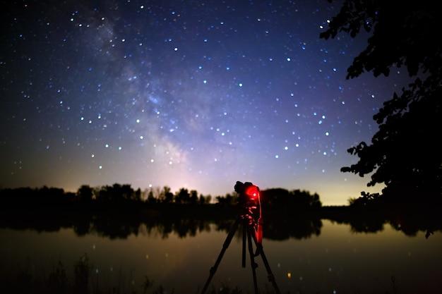 Aparat na statywie robi zdjęcia gwiazd otwartej przestrzeni na nocnym niebie.