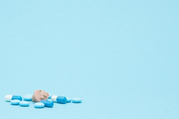 Aparat słuchowy i niebieskie tabletki na niebieskim tle. pojęcie medyczne, farmacji i opieki zdrowotnej
