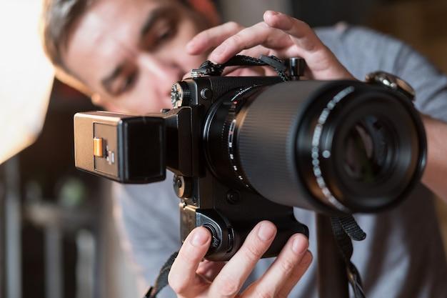 Aparat zbliżeniowy z lampą błyskową na tle fotografa