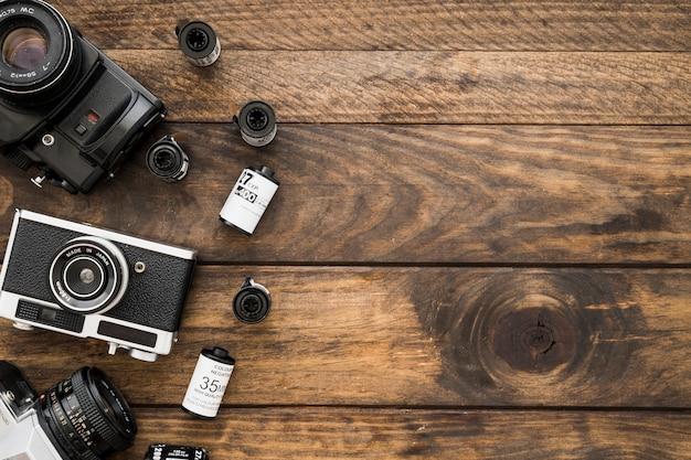 Aparaty fotograficzne i kasety z drewna na stole