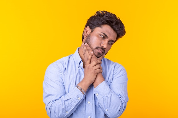 Apatyczny słodki młody indyjski mężczyzna pozuje na żółtej ścianie z miejscem na kopię i myśli o czymś. koncepcja niespełnionych marzeń.