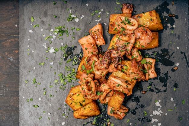 Aperitif lub typowa hiszpańska kałamarnica tapa baby z czosnkiem i ziemniakami na podłużnym białym