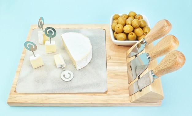 Aperitif na stole z oliwkami i świeżym holenderskim serem.