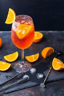 Aperol spritz koktajl i akcesoria barowe. włoski aperol spritz koktajl i plasterki pomarańczy na ciemnym tle. letni koktajl z aperolem na tablicy łupkowej
