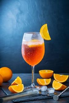 Aperol spritz koktajl i akcesoria barowe. włoski aperol spritz koktajl i plasterki pomarańczy na ciemnym tle. letni spritz z aperolem koktajlowym na tablicy łupkowej