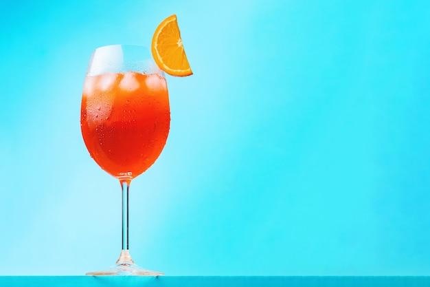Aperol spritz koktajl na niebieskim tle. szklanka spritz z aperolem koktajlowym z plasterkiem pomarańczy. włoski letni koktajl. orientacja pozioma
