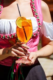 Aperol spritz koktajl szklany stół w kratę pozostawia słońce pomarańczowy wiadro lodu cień światło słoneczne dłoni