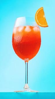 Aperol spritz koktajl z plasterkiem pomarańczy. szklanka koktajl aperol spritz na niebieskim tle. włoski letni koktajl w stylu minimalizmu. orientacja pionowa