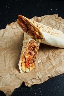 Apetyczna bułka shawarma z mięsem, sałatką i domowym sosem w cienkim chlebie pita na papierze rzemieślniczym na czarnej powierzchni. kuchnia wschodnia. kebab w plasterkach z grillowanym mięsem.