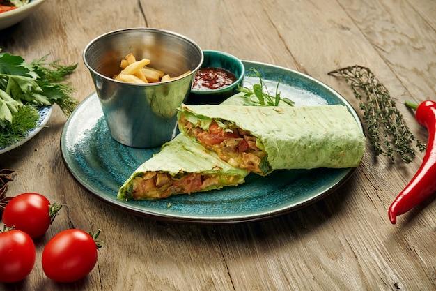 Apetyczna bułka shawarma z mięsem, sałatką i domowym sosem w cienkim chlebie pita w niebieskim talerzu na szarym tle. kuchnia wschodnia. kebab w plasterkach z grillowanym mięsem.