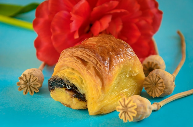 Apetyczna bułka z makiem ozdobiona cyjanowym kwiatkiem. piękne martwa natura z domowymi ciastami.
