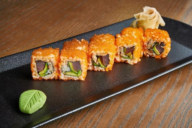 Apetyczna bułka z ryżem, kawiorem, tuńczykiem, awokado na czarnym talerzu na drewnianym. japońskie klasyczne rolki sushi. smaczne owoce morza. dodaj hałas po