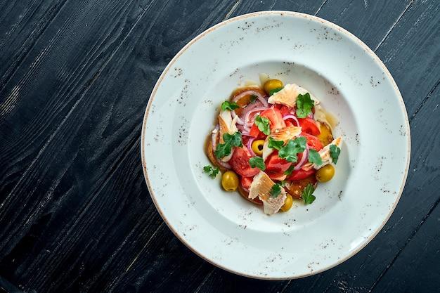 Apetyczna, dietetyczna sałatka z pomidorami, cebulą, oliwkami i pstrągiem z grilla w białym talerzu na ciemnej drewnianej powierzchni. zdrowe jedzenie